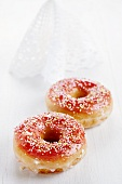 Two doughnuts with red glaze and sugar balls