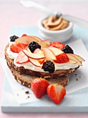 A slice of bread topped with cream cheese and fruit