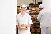 Bäckerin mit Brotlaiben, im Hintergrund Bäcker vor Brotregal