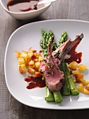 Saddle of lamb with roast potatoes and asparagus