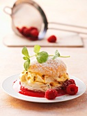 A brioche filled with mascarpone and passion fruit cream with raspberry sauce