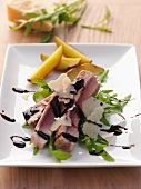 Tuna on a bed of rocket with Parmesan shavings and balsamic cream