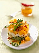 A salad tower made of avocado, mozzarella, mango and roasted pine nuts