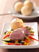 Pork fillet on bed of colourful vegetables with potato dumplings and caper sauce