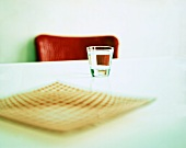 A glass of water and a plate on a table