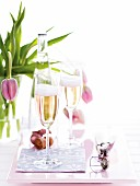 Two glasses of sparkling wine with a vase of tulips