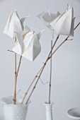 White paper flowers on twigs as a table decoration