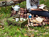 A woman with a book on a picnic blanket on an autumnal field