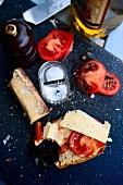 Angebissenes Tomaten-Käse-Brot auf Tisch mit Zutaten