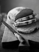 Bread, partly cut into slices (black and white image)