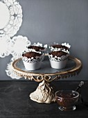 Chocolate muffins in decorative cases on a cake stand