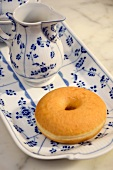 A doughnut and a jug of milk on a blue and white plate