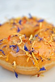 A doughnut decorated with dried flowers