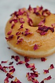 A doughnut decorated with dried rose petals