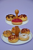 Doughnuts with various toppings on a cake stand