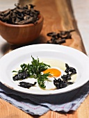 A fried egg with black chanterelles