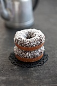 Two doughnuts with chocolate glaze and grated coconut