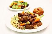 Beef Stroganoff with Noodles; Bun; Salad in Background
