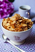 A bowl of cornflakes and raisins on a breakfast table