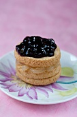 A shortbread petit four filled with lemon curd and blueberry jam