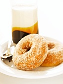 Two Sugared Donuts on a Plate; Glass of Flavored Milk