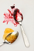 Apricot jam and cherry jam on spoons
