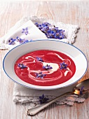 Beetroot soup with blue edible flowers