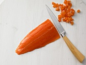 A fish fillet being diced