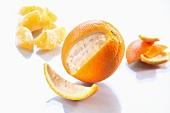 An orange, partially peeled, and orange segments