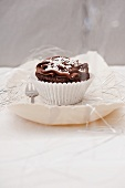 A chocolate cupcake decorated with white beads