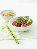 Meatballs in a sauce with coriander and oriental noodles