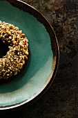 A chocolate and banana doughnut topped with nuts
