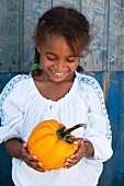 A little girl holding a pumpkin