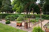 In historische Gartenanlage integrierter aber mit Maschendraht und antikem Torbogen abgegrenzter Nutzgarten mit Gemüsebeeten