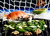Spinach salad with avocado and walnuts with a plastic crab in the background