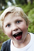 A boy sticking out his tongue which has been coloured with blueberries