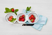 Fresh strawberries with leaves and flowers in bowls