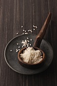 Round grain rice in a rustic wooden ladle