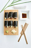 Tuna and cucumber sushi with soy sauce, wasabi and ginger