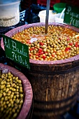 Preserved olives in wooden barrels at a market