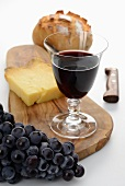 A glass of red wine, bread, cheese and grapes