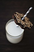 A glass of milk with a straw and a chocolate biscuit