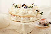 Meringue Cake with Edible Flowers on a White Pedestal Dish