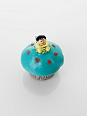 A turquoise cupcake decorated with a bee