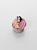 A cupcake decorated with strawberry cream and penguin
