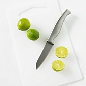 Whole and Halved Key Limes with a Knife on a White Cutting Board