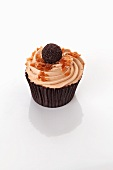 A cupcake decorated with a chocolate praline