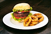 A beefburger with fried onion rings