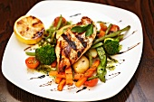 Grilled chicken breast on a bed of vegetables
