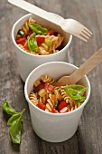 Fusilli with tomatoes, courgette and basil in paper cups